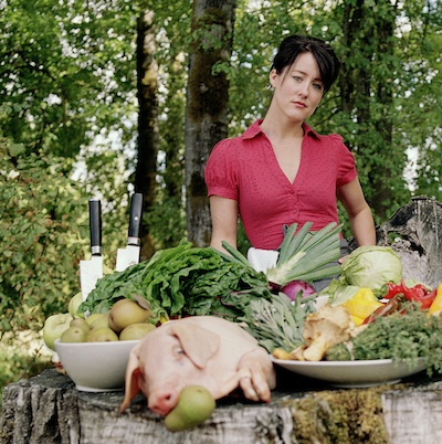 Naomi Pomeroy in a red shirt stands with a table spread of vegetables, fruit, and a suckling pig